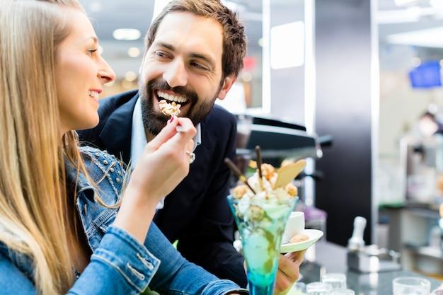 Paar die van een roomijsijscoupe in koffie genieten