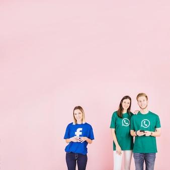 Paar die whatsapp t-shirt dragen die zich naast vrouw bevinden die facebook bovenkant dragen