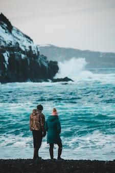 Paar die zich bij de rotsvorming dichtbij watermassa overdag bevinden