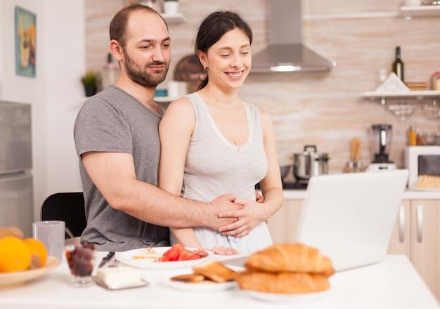 Paar doen online winkelen op laptop tijdens het ontbijt. informatie invoeren, klant die e-commercetechnologie gebruikt om dingen op internet te kopen, cosumerisme bankieren en bestellen