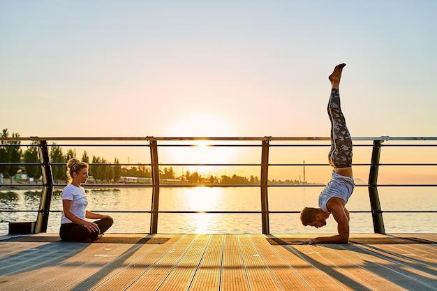 Paar doen samen yoga beoefenen op de natuur buiten ochtendoefeningen bij de zonsopgang