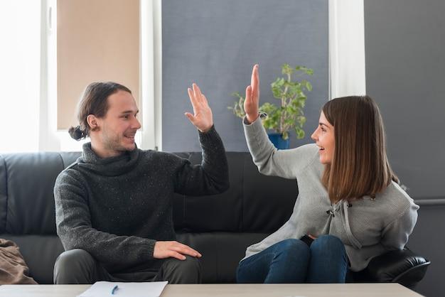 Paar doet high five op de bank