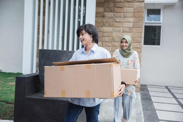 Paar dragen kartonnen doos verhuizen naar nieuw huis