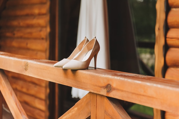 Paar eenvoudige elegante trouwschoenen met hoge hakken en een trouwjurk