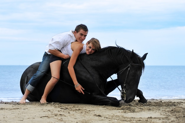 Paar en paard op het strand