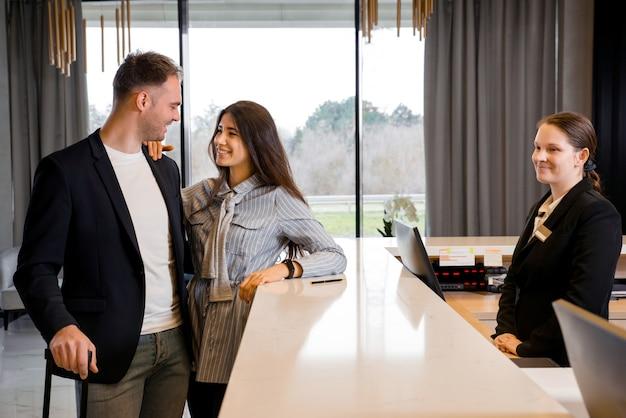 Paar en receptioniste bij balie in hotel. jong stel op zakenreis die inchecken in het hotel