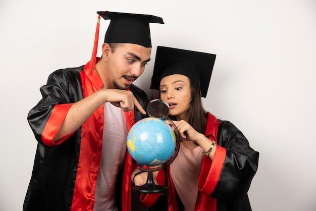 Paar enthousiaste studenten die in toga bol met vergrootglas bekijken.