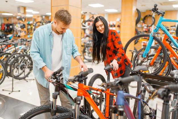 Paar fietsen kiezen, winkelen in sportwinkel.