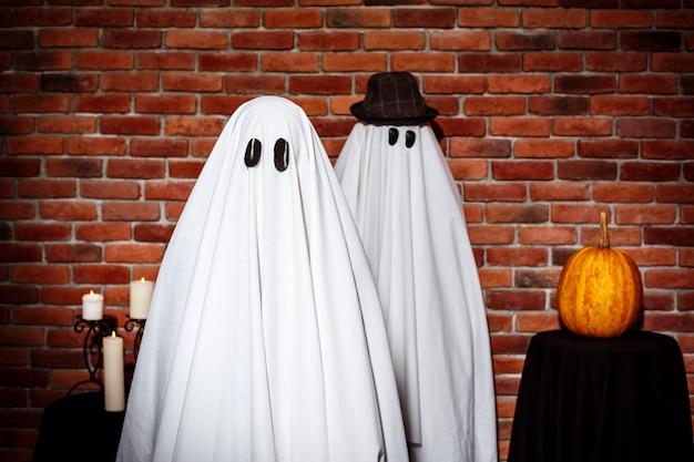 Paar geesten poseren over bakstenen muur. halloween feest.