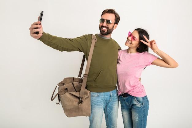 Paar geïsoleerde, vrij lachende vrouw in roze t-shirt en man in sweatshirt met reistas, spijkerbroek en zonnebril dragen, plezier hebben, samen reizen maken van grappige selfie foto op telefoon