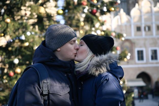 Paar geliefden kussen op de achtergrond van een kerstboom