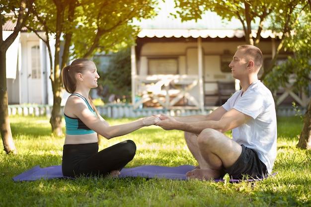 Paar geliefden zitten op een tapijt voor yoga en houden elkaars hand vast. ochtend in de zomertuin