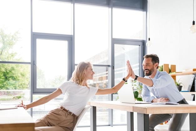 Paar gelukkige collega's die high five geven