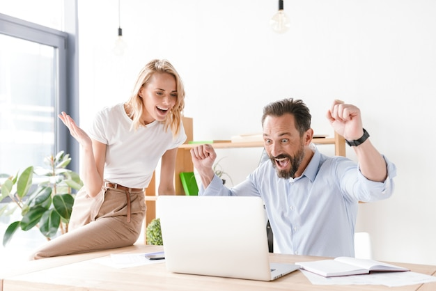 Paar gelukkige collega's die succes vieren