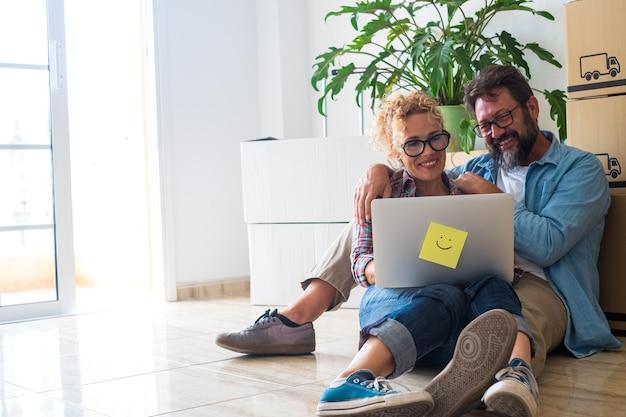 Paar gelukkige mensen die plezier hebben en samen een laptop gebruiken die op het net surft - twee volwassenen nadat ze een nieuw huis hebben gekocht, zittend op de vloer met hun dozen en pakketten op hun rug