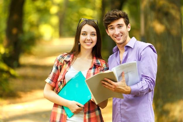 Paar gelukkige studenten met boeken in het park op een zonnige dag