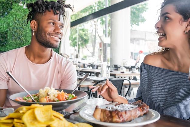 Paar genieten en samen goede tijd doorbrengen terwijl ze een date hebben in een restaurant.