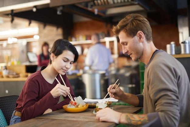 Paar genieten van aziatisch eten in cafe