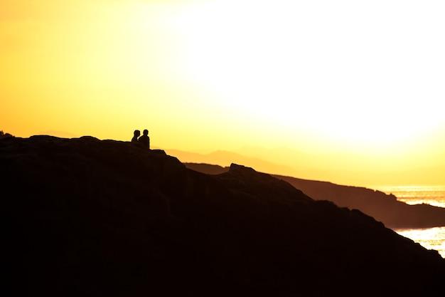 Paar genieten van de zonsondergang aan de kust