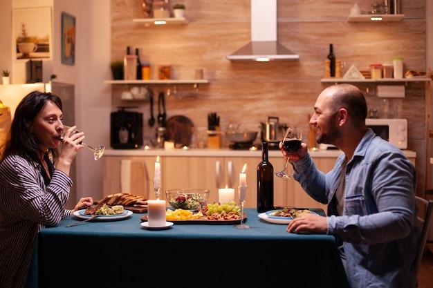 Paar genieten van een glas wijn. gelukkig paar praten, aan tafel zitten in de eetkamer, genieten van de maaltijd, hun jubileum thuis vieren met romantische tijd.