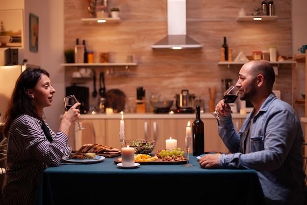 Paar genieten van een glas wijn. ontspan gelukkige mensen die rammelen, aan tafel zitten in de keuken, genieten van de maaltijd, jubileum vieren in de eetkamer.