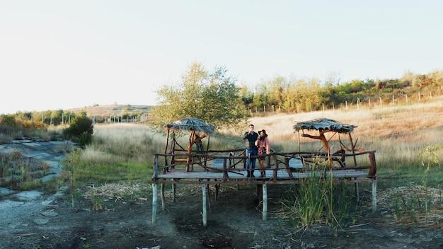Paar genieten van een glas wijn op een ponton op het platteland zijn in de buurt van een meer, drone-opnames vanuit de lucht