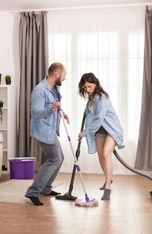 Paar genieten van het schoonmaken van hun huis met behulp van vacuüm en dweil