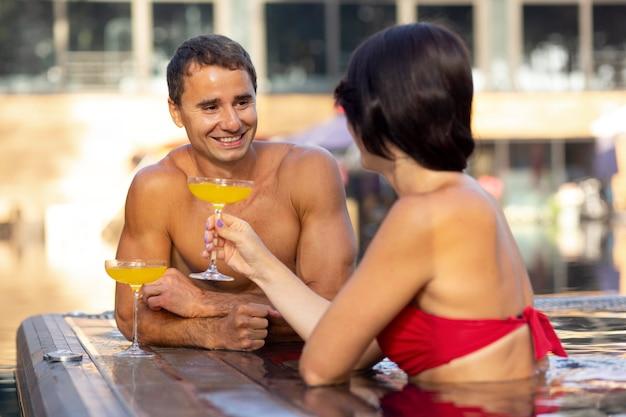 Paar genieten van hun dag bij het zwembad met drankjes