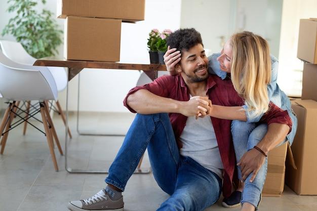 Paar genieten van hun nieuwe luxe huis en knuffelen in de woonkamer