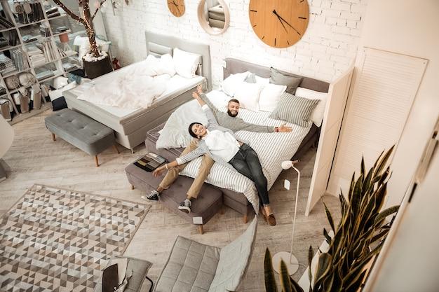 Paar genieten van proces. vrolijk knap stel dat in de showroom ronddoolt tijdens het zoeken naar meubels voor de slaapkamer