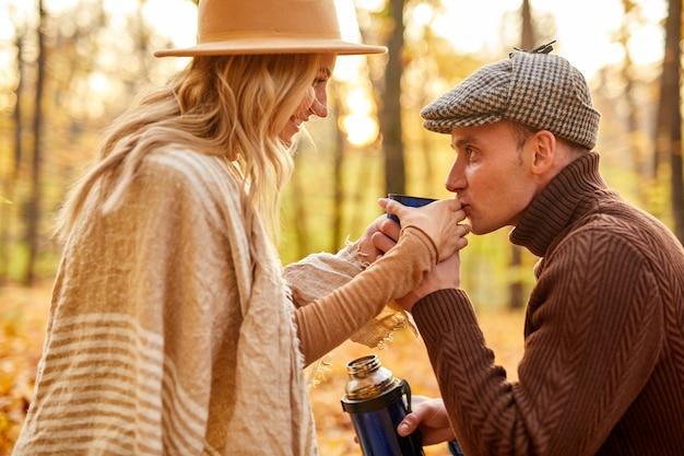 Paar genieten van thee buiten in het park, kaukasische getrouwde man en vrouw hebben romantische tijd