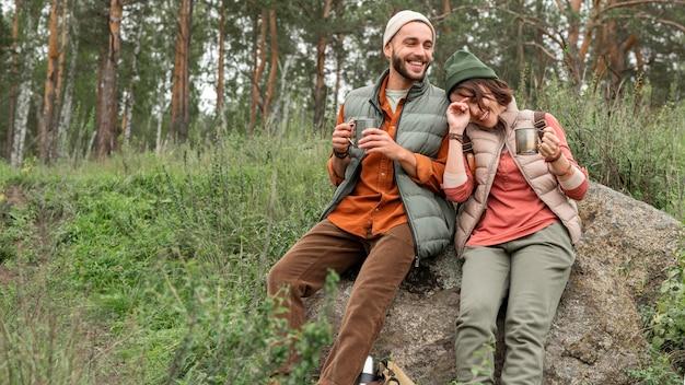 Paar genieten van warme drank in de natuur