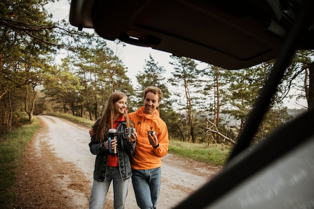 Paar genieten van warme drank tijdens een roadtrip met de auto