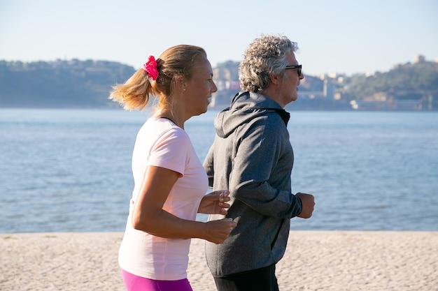 Paar gepensioneerden die sportkleding dragen, genieten van 's ochtends hardlopen, joggen langs de rivieroever in de ochtend. zijaanzicht. levensstijl en pensioen concept