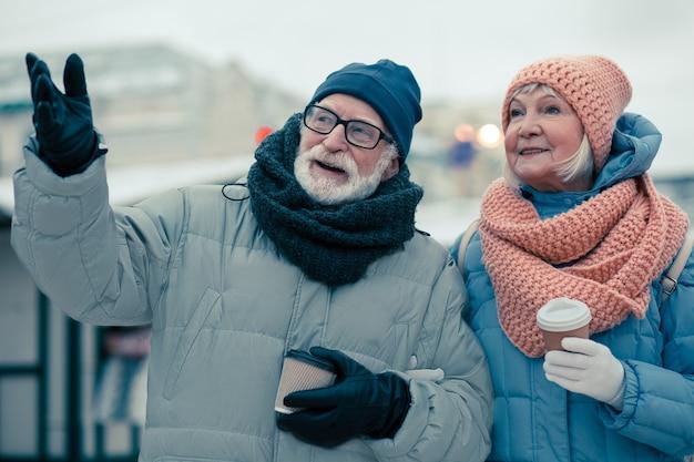 Paar gepensioneerden in winterkleren met kartonnen bekers in hun handen. man gebaren en wegkijken tijdens het praten