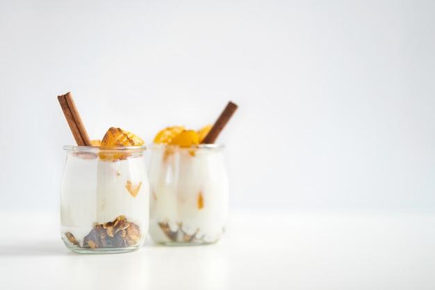 Paar glazen potten griekse yoghurt met granola, kaneel en ingeblikte abrikozen