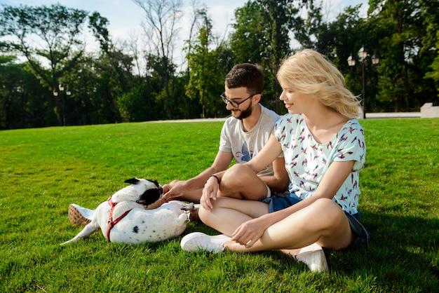 Paar glimlachen, die op gras met franse buldog in park zitten