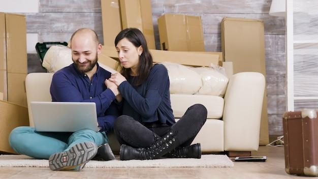Paar glimlachen terwijl ze op de vloer van hun nieuwe appartement zitten en online winkelen met een laptop.