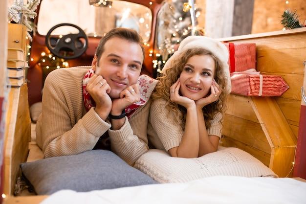 Paar glimlachend en genieten van hun tijd samen in pick-up auto. kerstverlichting op de achtergrond.