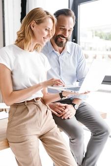 Paar glimlachende collega's die aan laptop werken