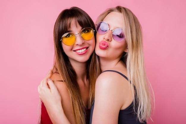 Paar glimlachende vrouwen die kus verzenden en op roze muur stellen