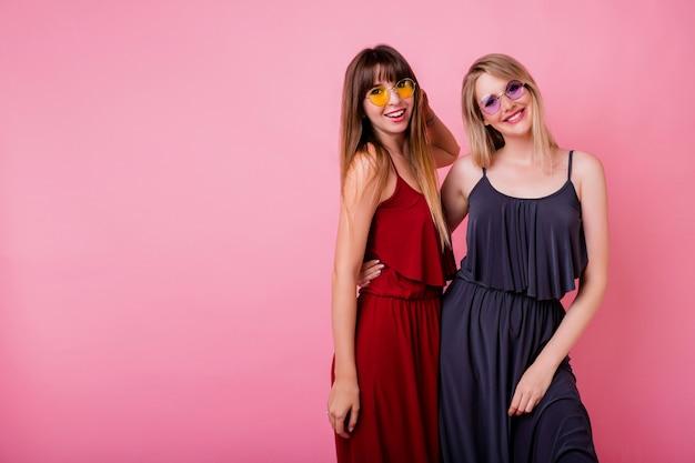 Paar glimlachende vrouwen die op roze muur stellen