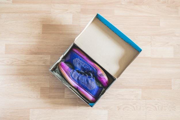 Paar gloednieuwe schoenen in cartoon schoenendoos op houten vloer f