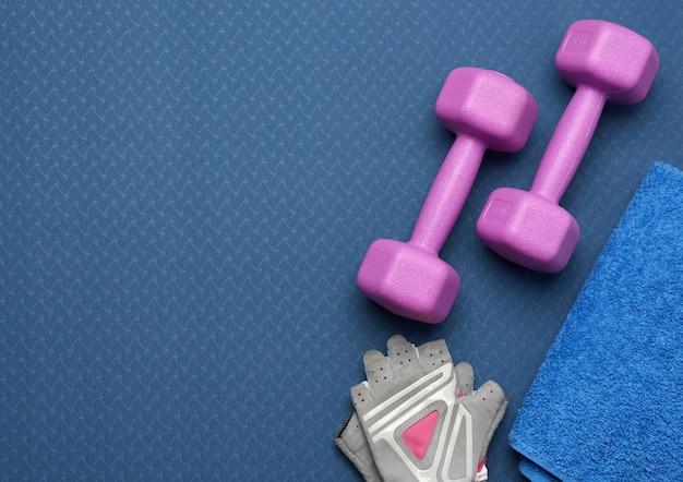 Paar halters, sporthandschoenen en blauwe handdoek, bovenaanzicht, set