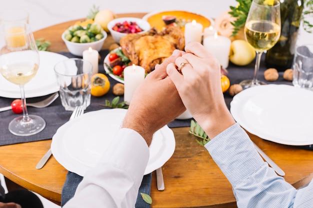 Paar hand in hand aan tafel