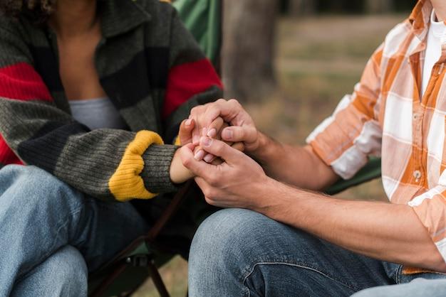 Paar hand in hand buitenshuis tijdens het kamperen