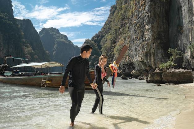 Paar hand in hand en lopen op het strand van phi phi, genieten van mooie zomervakantie. reizen vakantie levensstijl concept