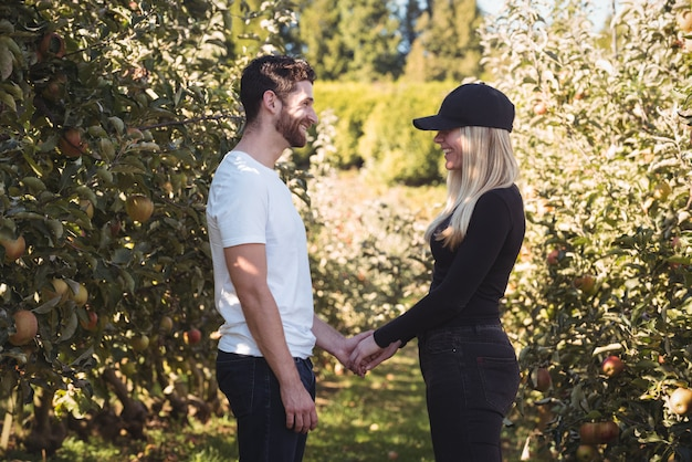 Paar hand in hand en staande in appelboomgaard