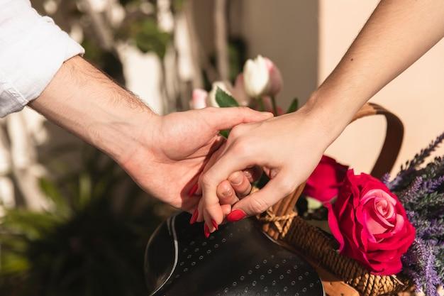 Paar hand in hand met mand met bloemen