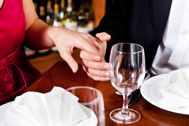 Paar hand in hand op een restaurant tafel
